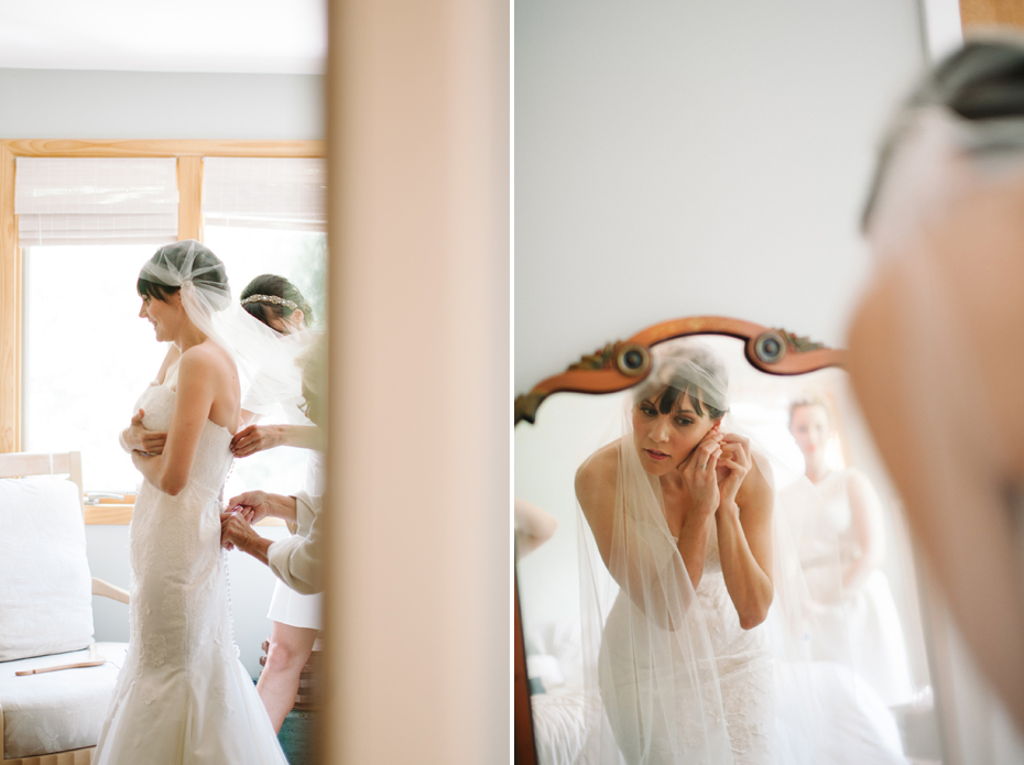 A bride is helped into her wedding dress by her bridesmaids and mother in this photograph by Ann Arbor Michigan wedding photographer, Heather Jowett.