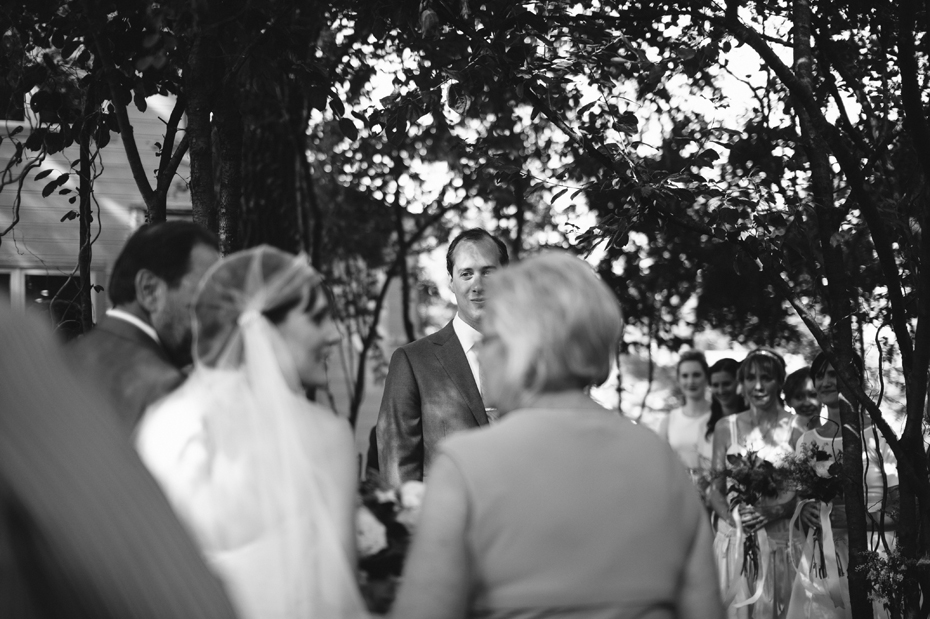 The groom sees his bride for the first time in their backyard wedding ceremony by Detroit Michigan wedding photographer, Heather Jowett.