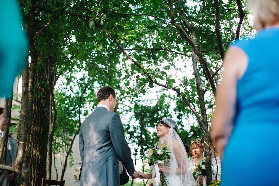 Bride and groom share a laugh during their backyard wedding ceremony by Detroit Michigan wedding photographer, Heather Jowett.