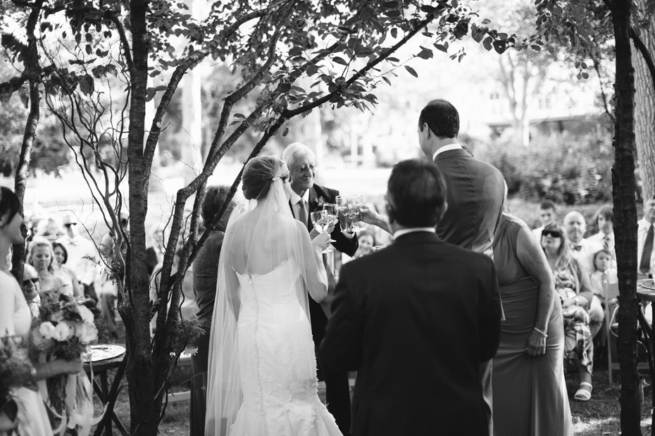Bride and groom participate in a wine ceremony during A backyard wedding by Detroit Michigan wedding photographer, Heather Jowett.