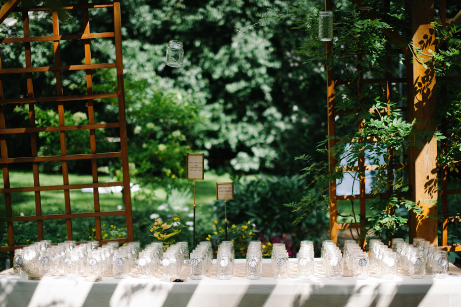 Mason jar escort cards at a backyard wedding reception by Ann Arbor Michigan wedding photographer, Heather Jowett.
