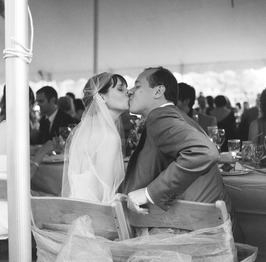 Black and white photo of the bride and groom at their backyard wedding reception by Ann Arbor Michigan wedding photographer, Heather Jowett.