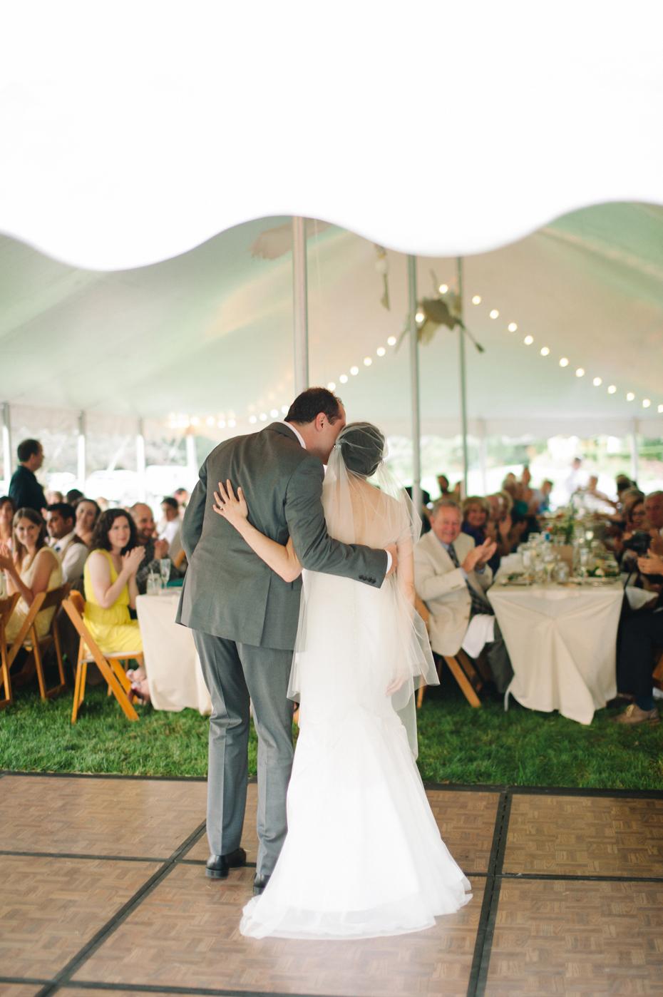 bride and groom share their first dance at their backyard wedding reception by Ann Arbor Michigan wedding photographer, Heather Jowett.