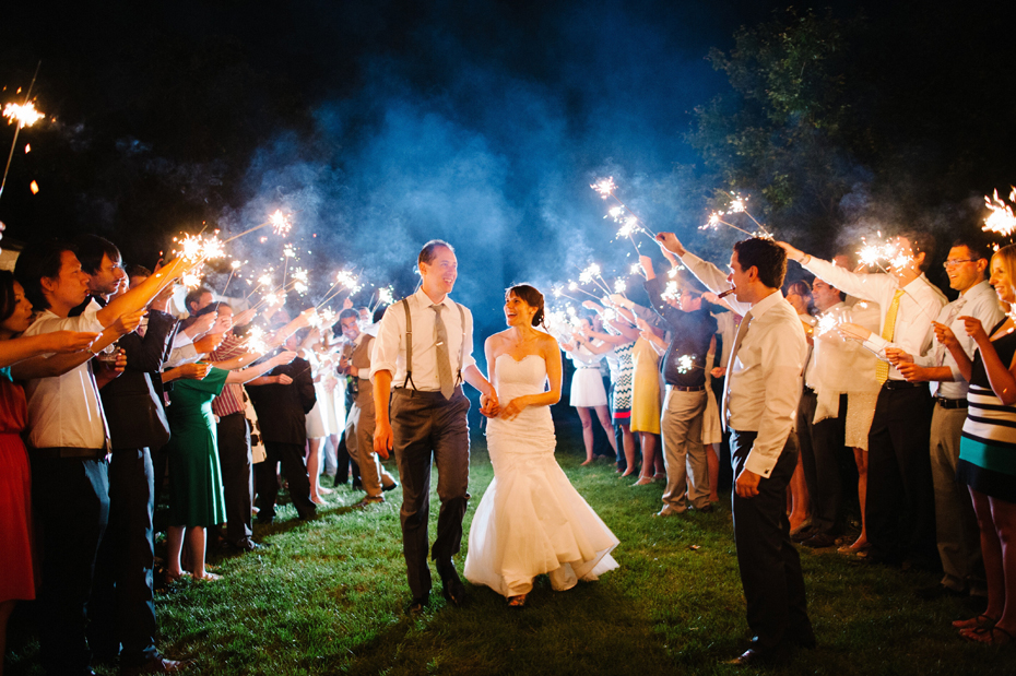 The bride and groom exit their wedding reception while guests hold sparklers at a backyard wedding by Bloomfield Hills wedding photographer Heather Jowett.