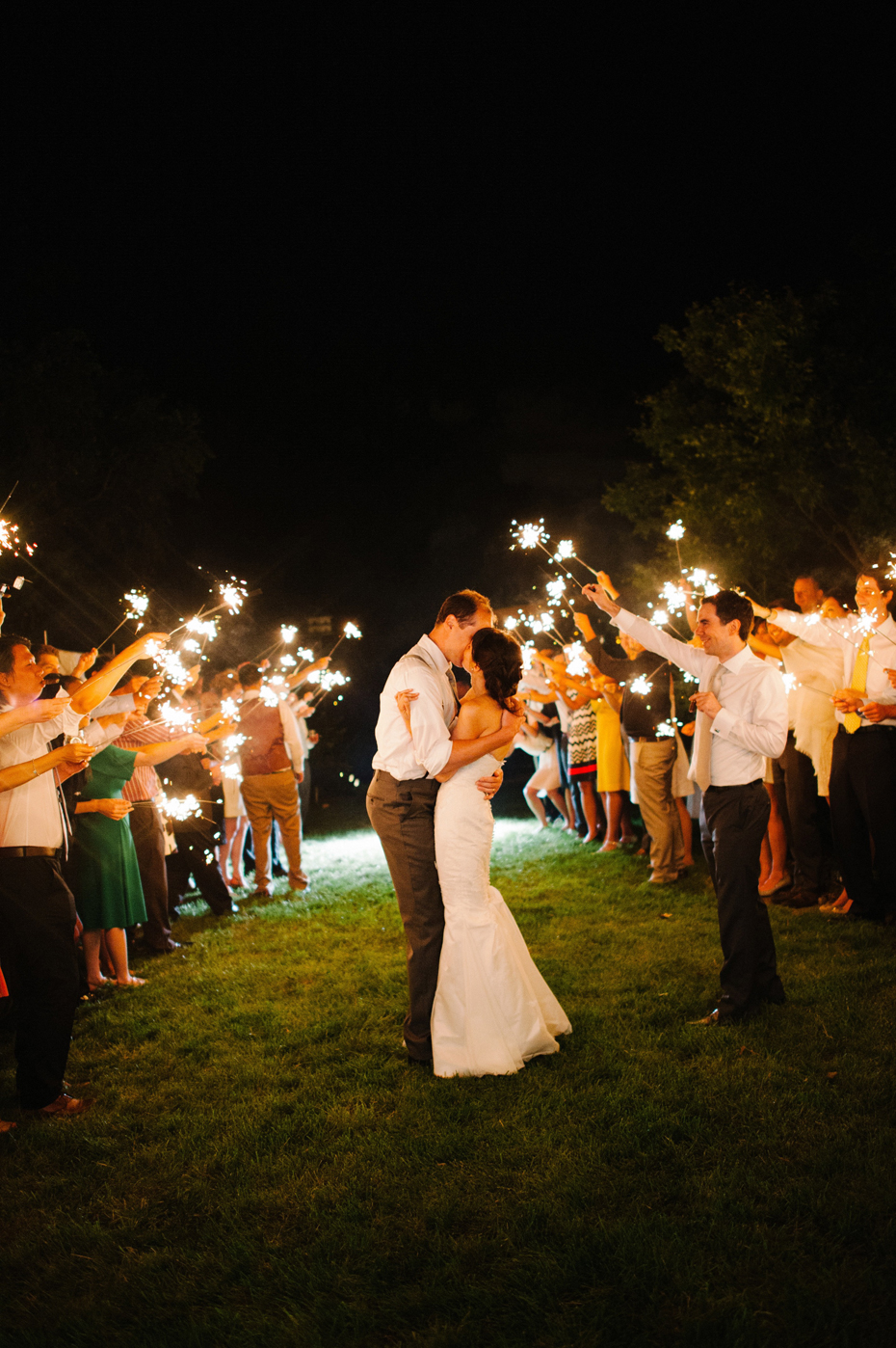 The bride and groom share one more kiss and then exit their wedding reception while guests hold sparklers at a backyard wedding by Bloomfield Hills wedding photographer Heather Jowett.