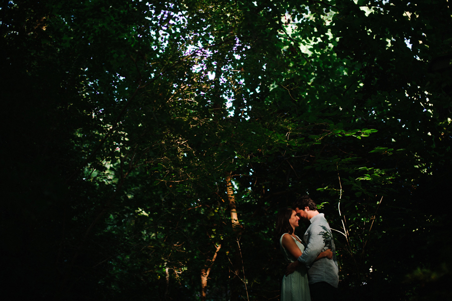 A couple embraces in the woods during a Newport News Virginia engagement session by Ann Arbor Wedding Photographer Heather Jowett.