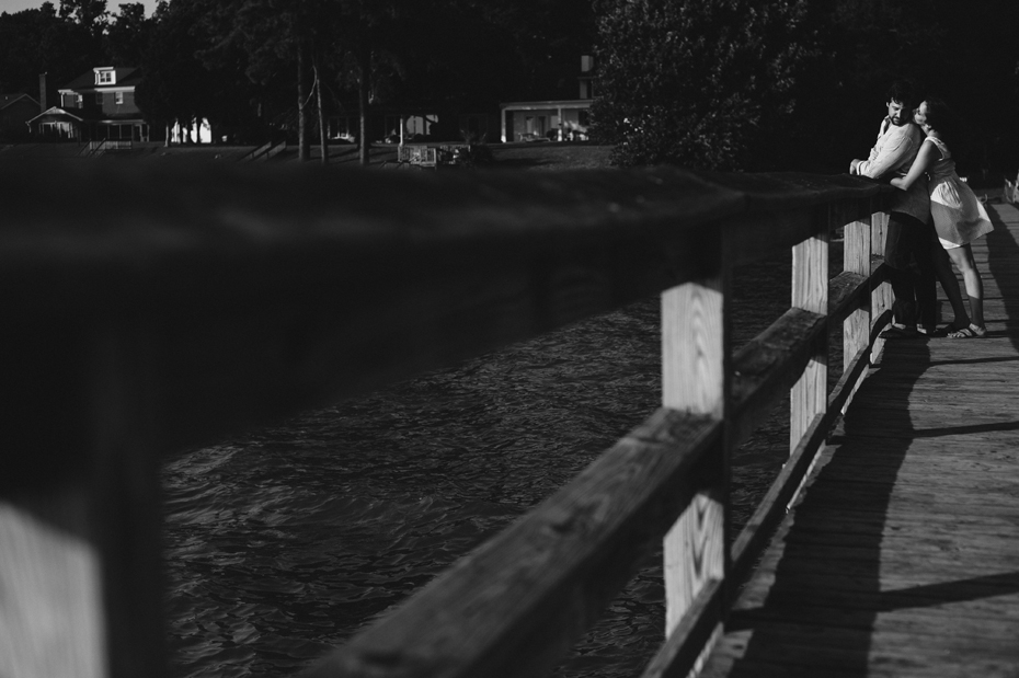 A couple poses on a dock behind of Hilton Elementary School during a Newport News Virginia engagement session by Ann Arbor Wedding Photographer Heather Jowett.