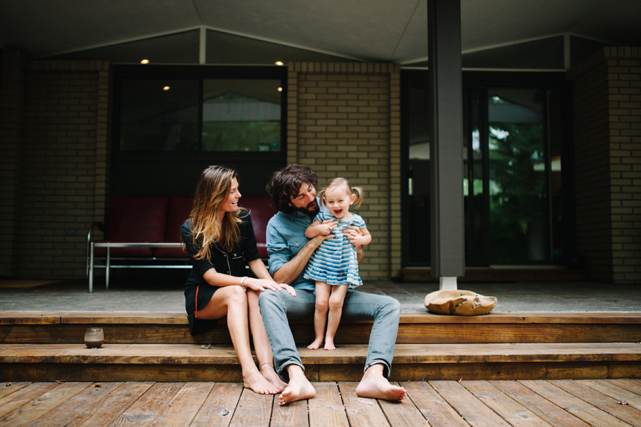 A family poses on their back deck during a lifestyle family portrait session in Ferndale photographed by Ann Arbor Wedding Photographer, Heather Jowett.