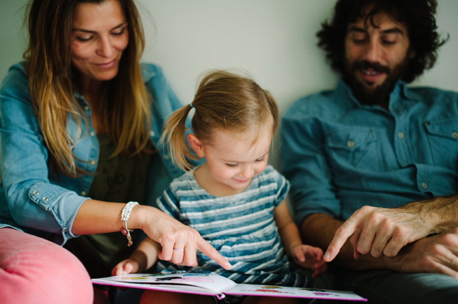 A family reads a story during a lifestyle family portrait session in Ferndale photographed by Ann Arbor Wedding Photographer, Heather Jowett.