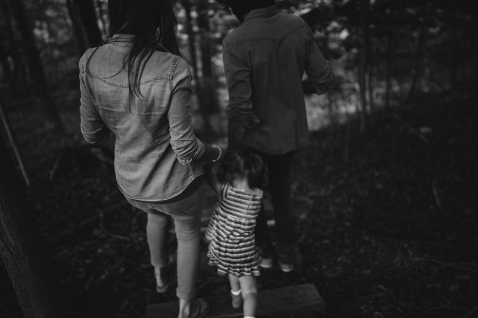 A family journeys to the creek that runs behind their house during a documentary family portrait session in Ferndale photographed by Ann Arbor Wedding Photographer, Heather Jowett.