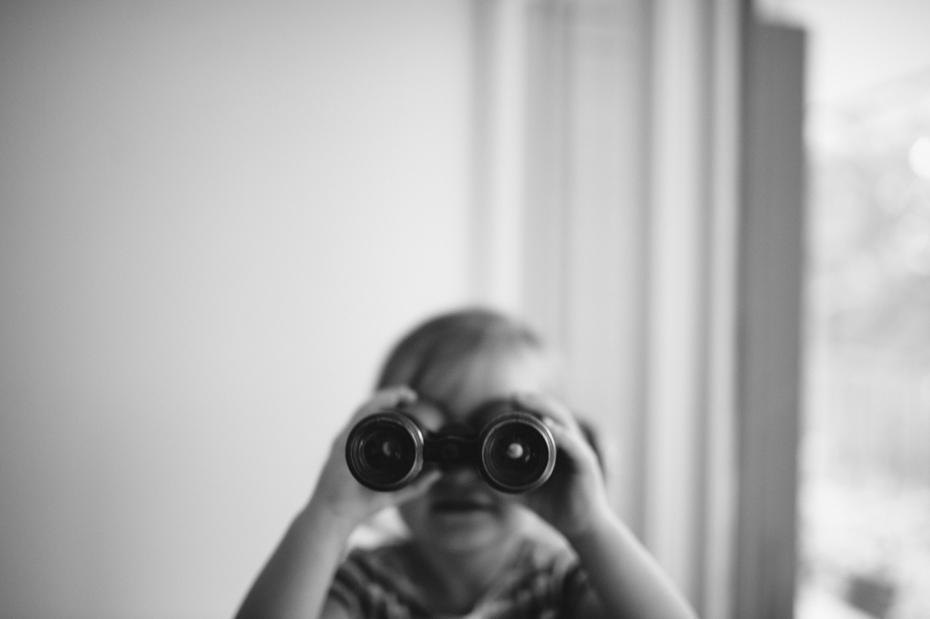 A two year old plays with binoculars during a documentary family portrait session in Ferndale photographed by Ann Arbor Wedding Photographer, Heather Jowett.
