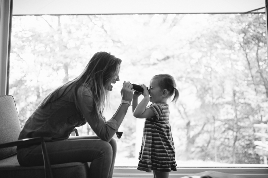 A two year old and her mother play with binoculars during a documentary family portrait session in Ferndale photographed by Ann Arbor Wedding Photographer, Heather Jowett.