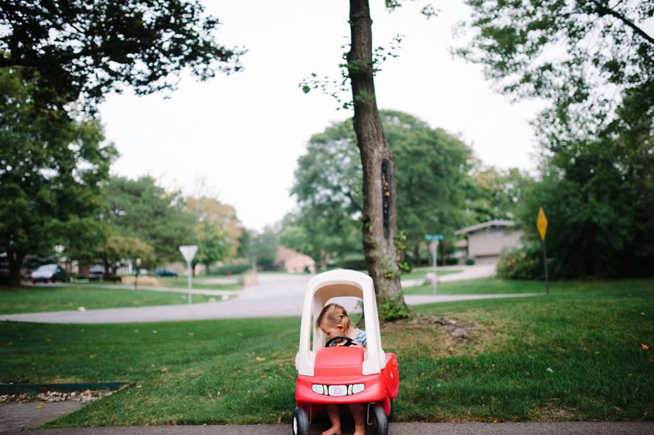 A two year old drives a toy car during a photojournalistic family portrait session in Ferndale photographed by Ann Arbor Wedding Photographer, Heather Jowett.