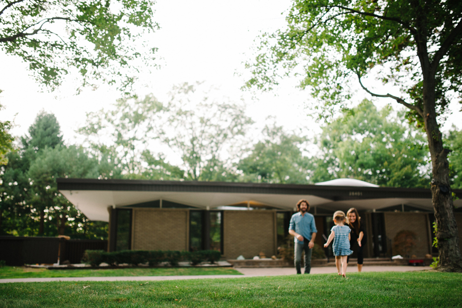 A two year old plays with her mother and father in the front yard of their mid-century home in Metro-Detroit during a photojournalistic family portrait session in Ferndale photographed by Ann Arbor Wedding Photographer, Heather Jowett.