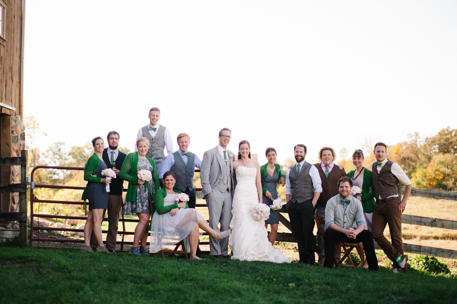 The wedding party poses by the barn at Misty Farms by photojournalistic Michigan wedding photographer Heather Jowett.