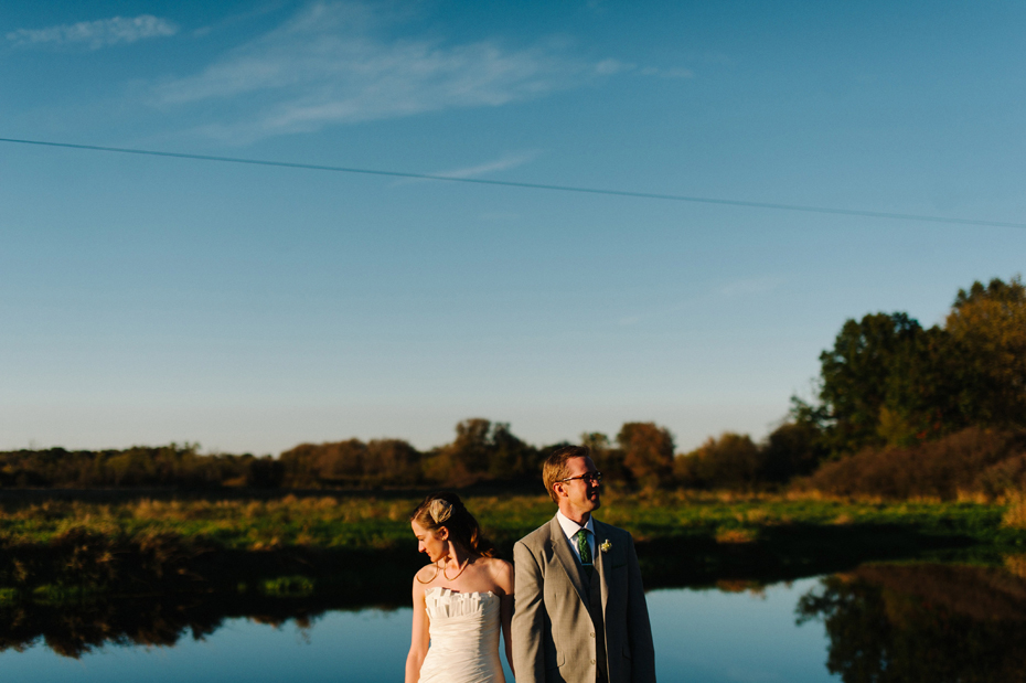 Bride and groom pose by the pond at Misty Farms in Ann Arbor MI.