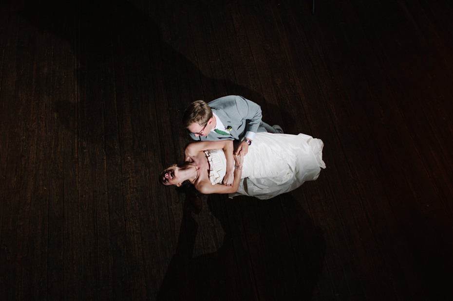 Bride and groom share a first dance in the barn at a wedding reception at Misty Farms by photojournalistic Michigan wedding photographer Heather Jowett.