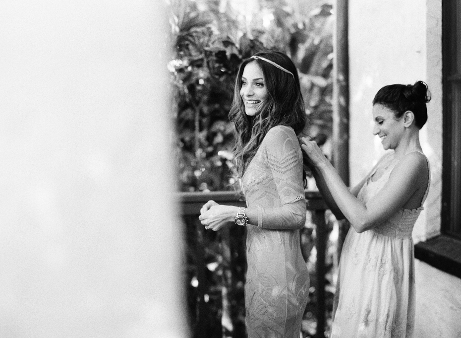 Bride's sister helps her get dressed in her red Roberto Cavalli dress for her wedding at the Sundy house by wedding photographer Heather Jowett.
