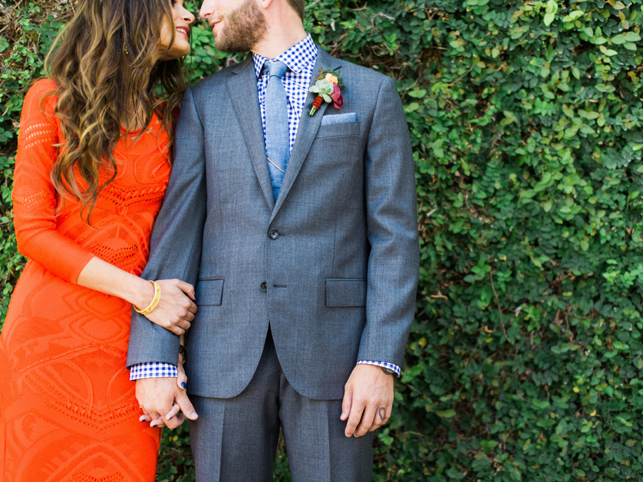 A groom in a grey suit and bride in a red Roberto Cavalli dress at the Sundy house in southern florida by wedding photographer Heather Jowett.