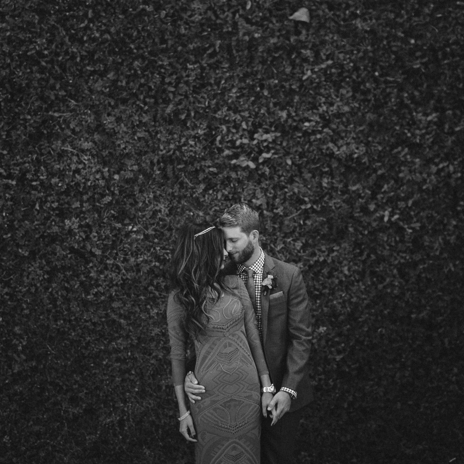 Moody black and white portrait of bride and groom against ivy at the Sundy House.