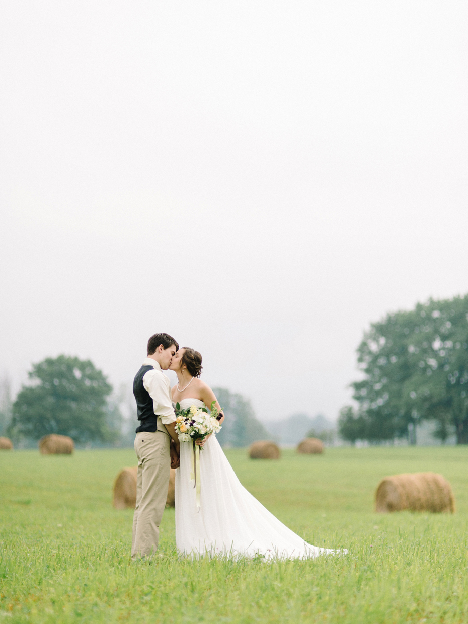 Bride and groom pose for portraits in a hayfield in Northern Michigan by Ann Arbor Wedding Photographer Heather Jowett.