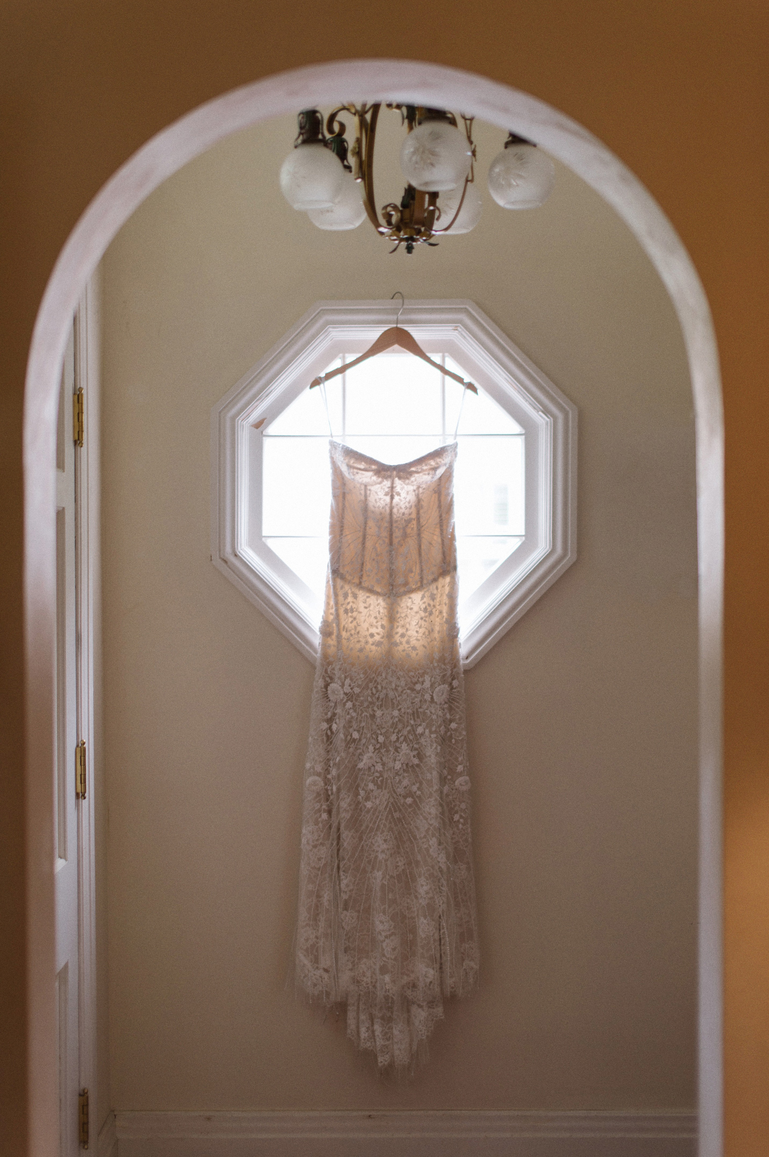 A bride's form fitting Monique Lhuillier gown hangs on the morning of her wedding day.