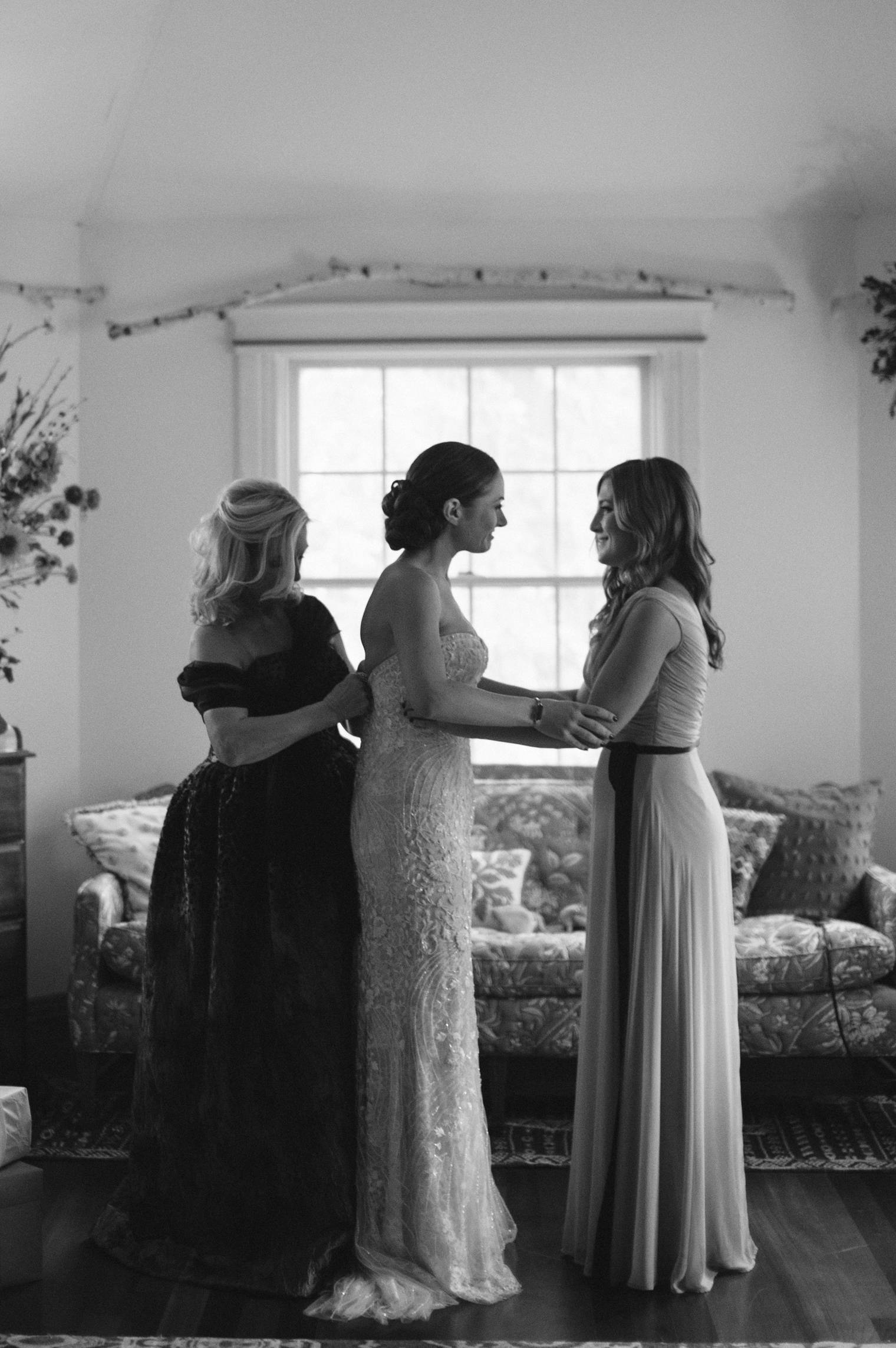 The mother of the bride and maid of honor help a bride into her Monique Lhuillier gown.