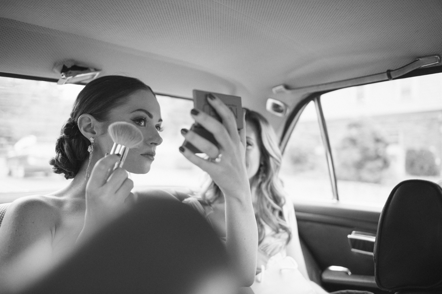 Bride touches up makeup in the back of a classic Mercedes.