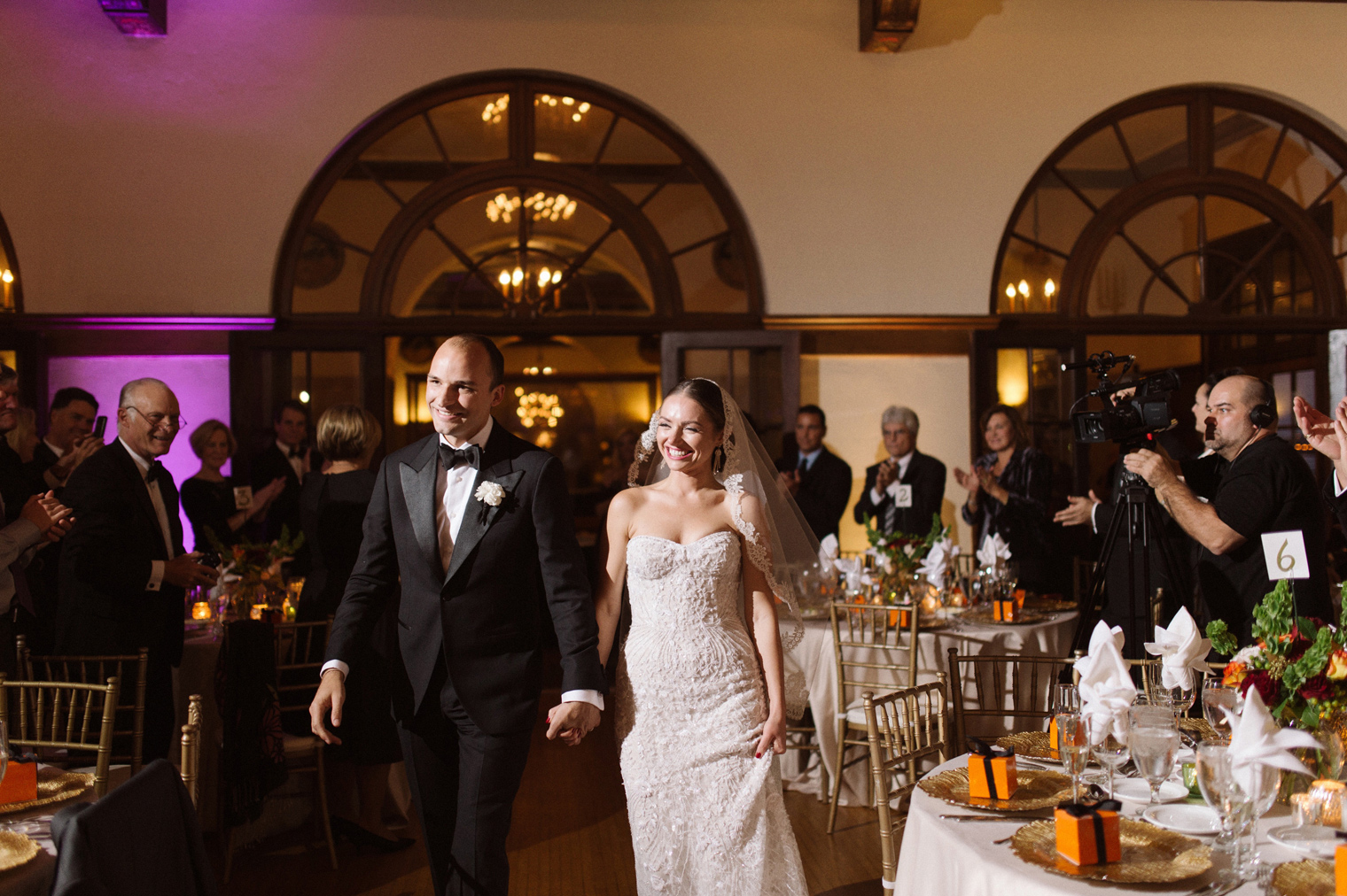 Bride and groom enter their Detroit Yacht Club wedding reception by Photographer Heather Jowett.