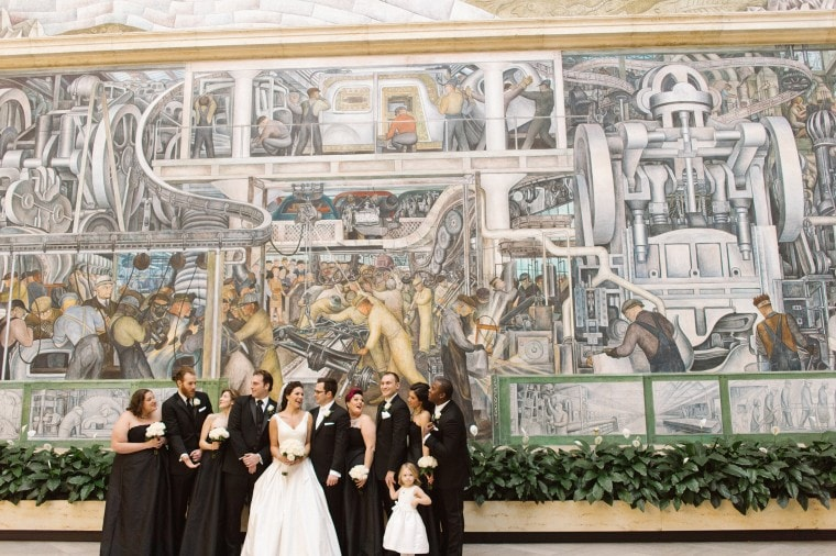 The wedding party poses for a photograph in the Rivera court of the Detroit Institute of Arts.