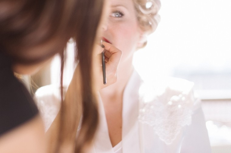 A bride puts on red lipstick at the Westin in Detroit.