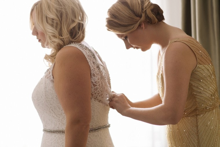 The maid of honor helps the bride into her wedding dress before her Gem Theater wedding in Detroit,