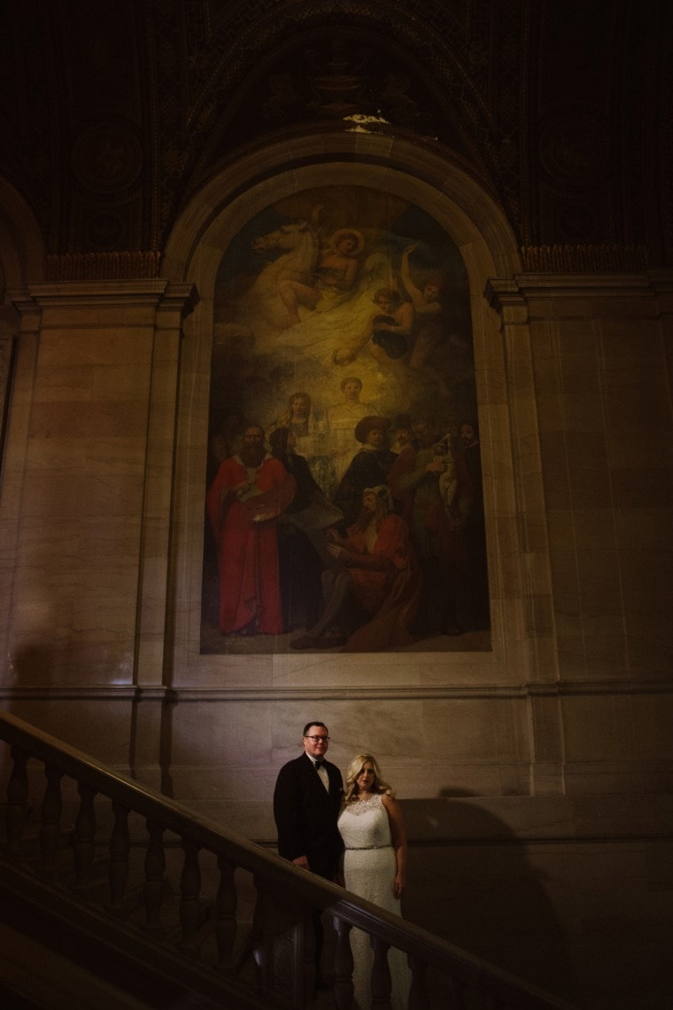 A bride and groom pose for portraits inside the Detroit public library.