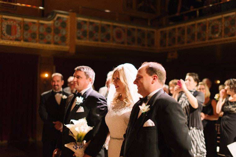 Bride is given away by her brothers at a wedding ceremony at the Gem Theater in Detroit