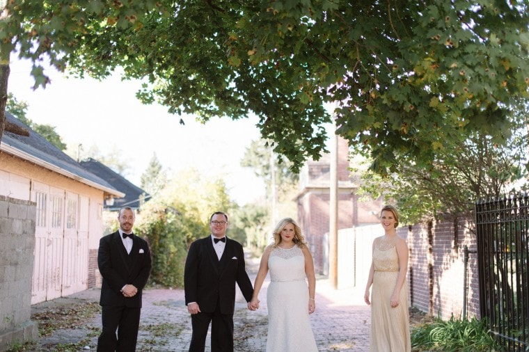 Bride and groom, along with their wedding party, take portraits in Detroit's Indian Village Neighborhood.