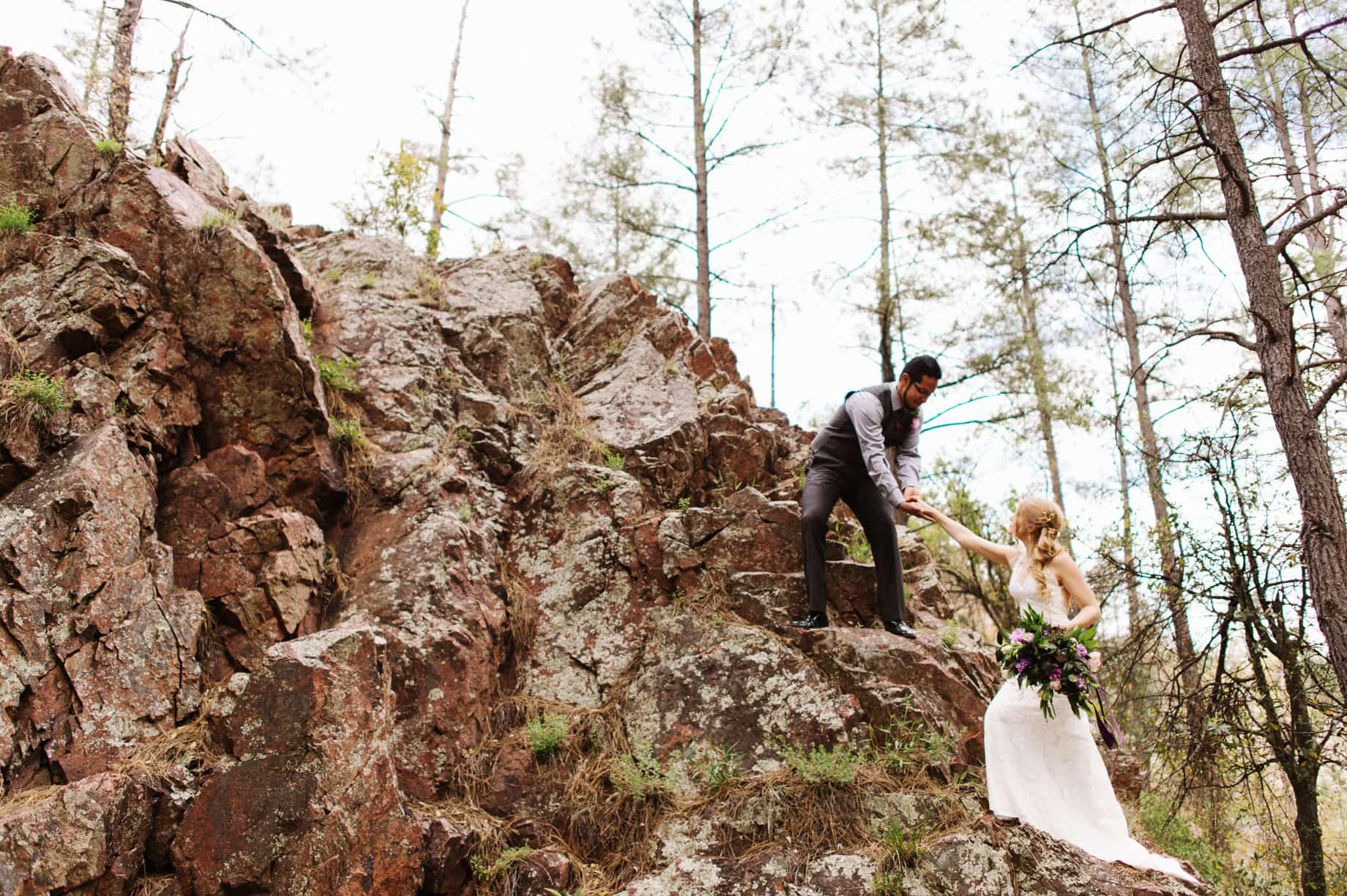 hiking climbing bride and groom