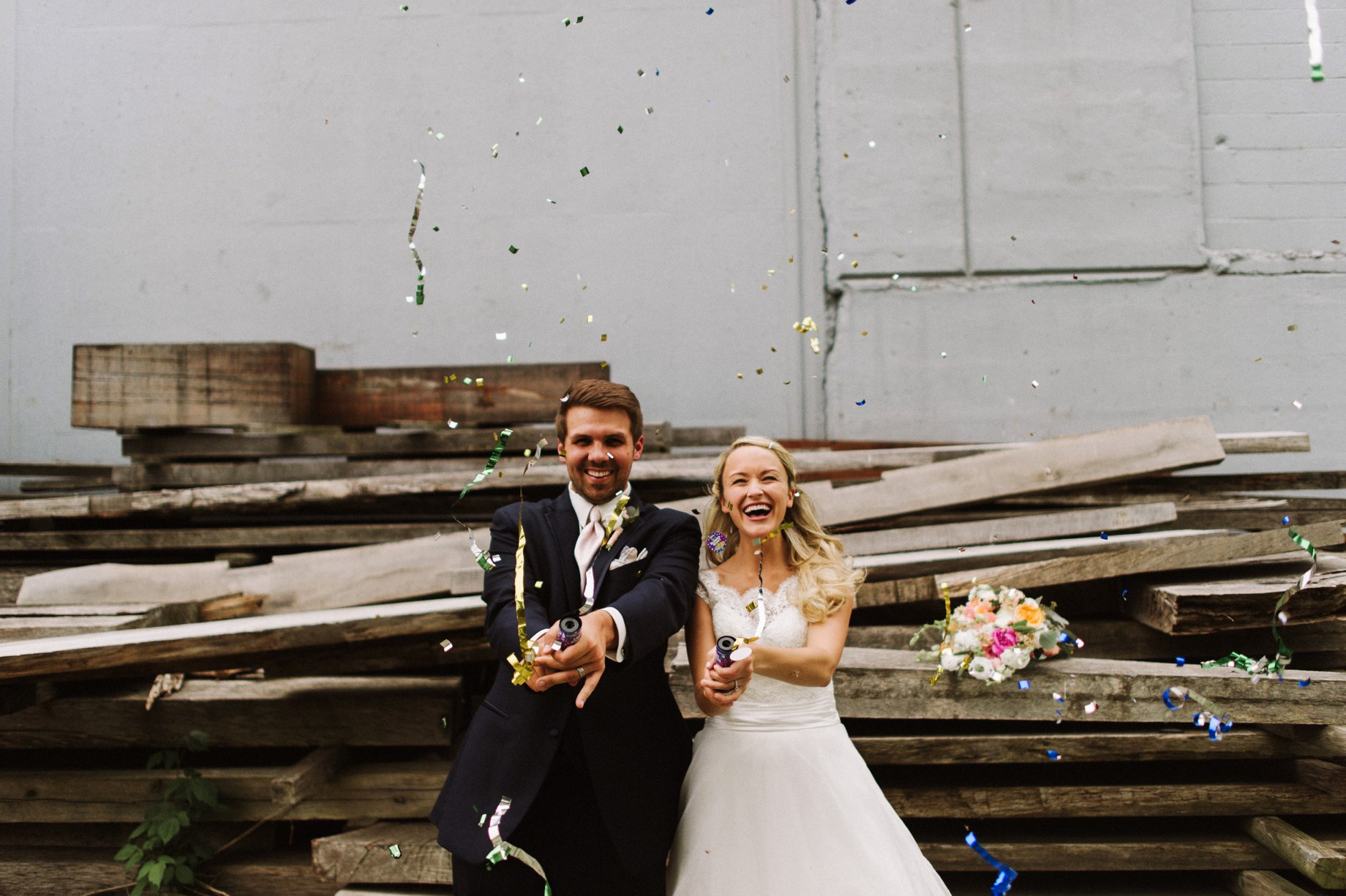 bride and groom with confetti poppers