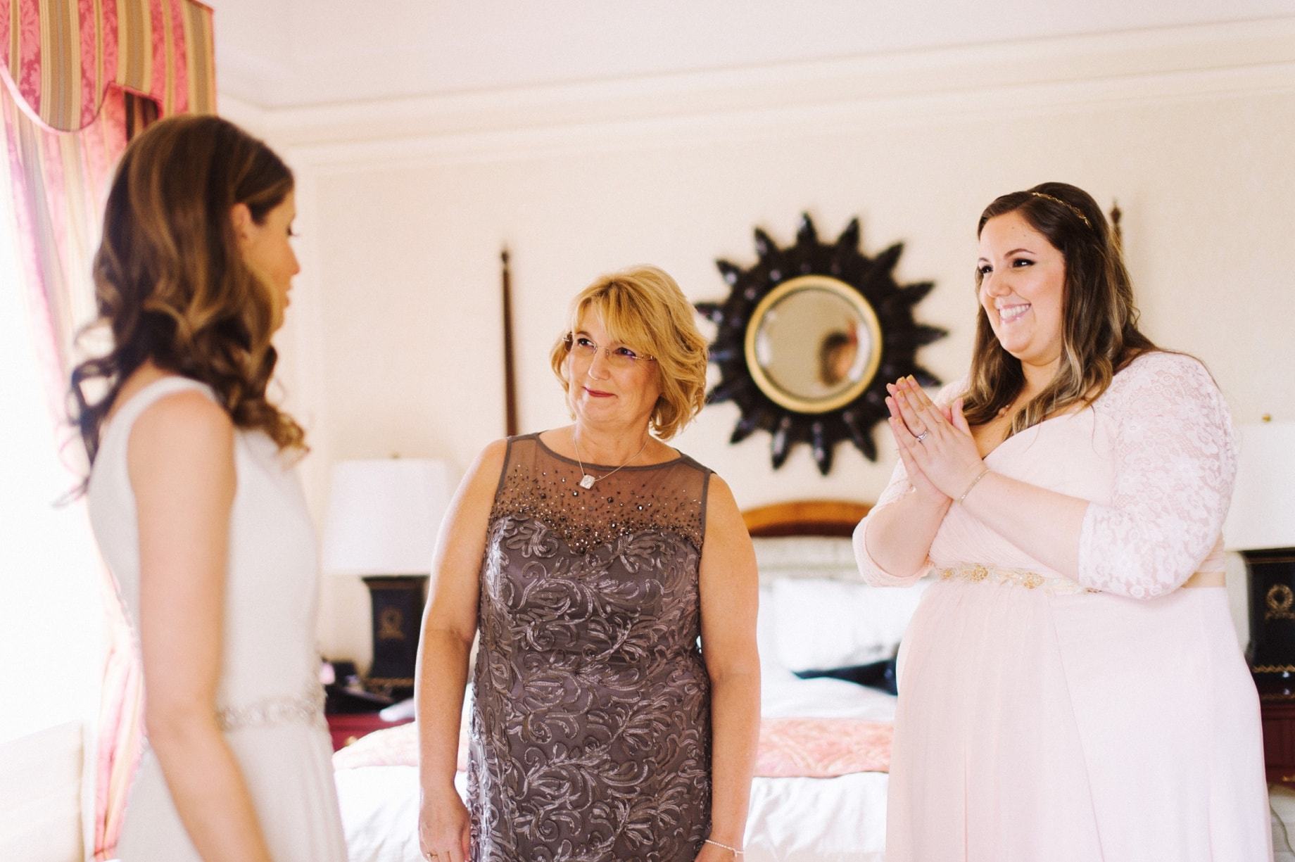 mother and sister seeing bride in dress