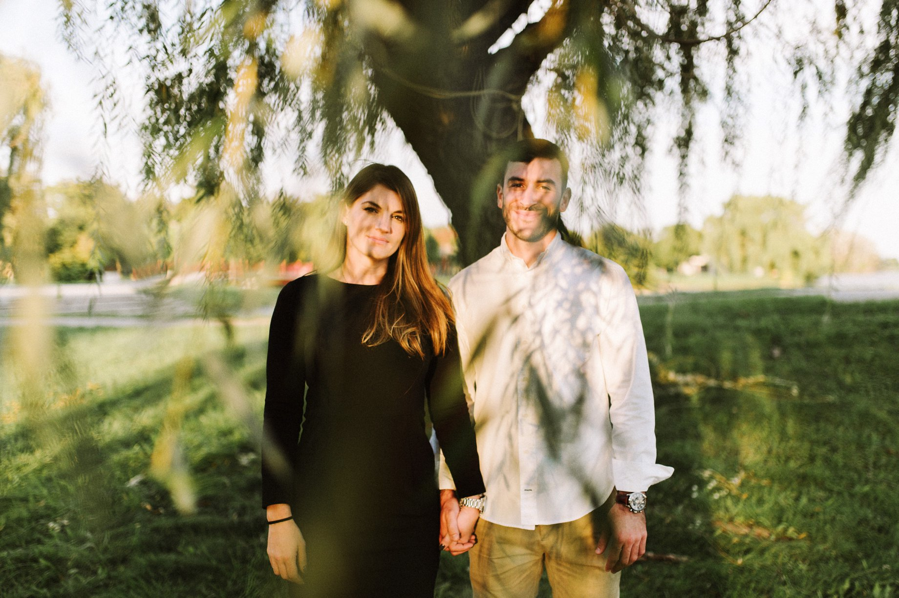 couple posing for engagement photographs in a willow tree