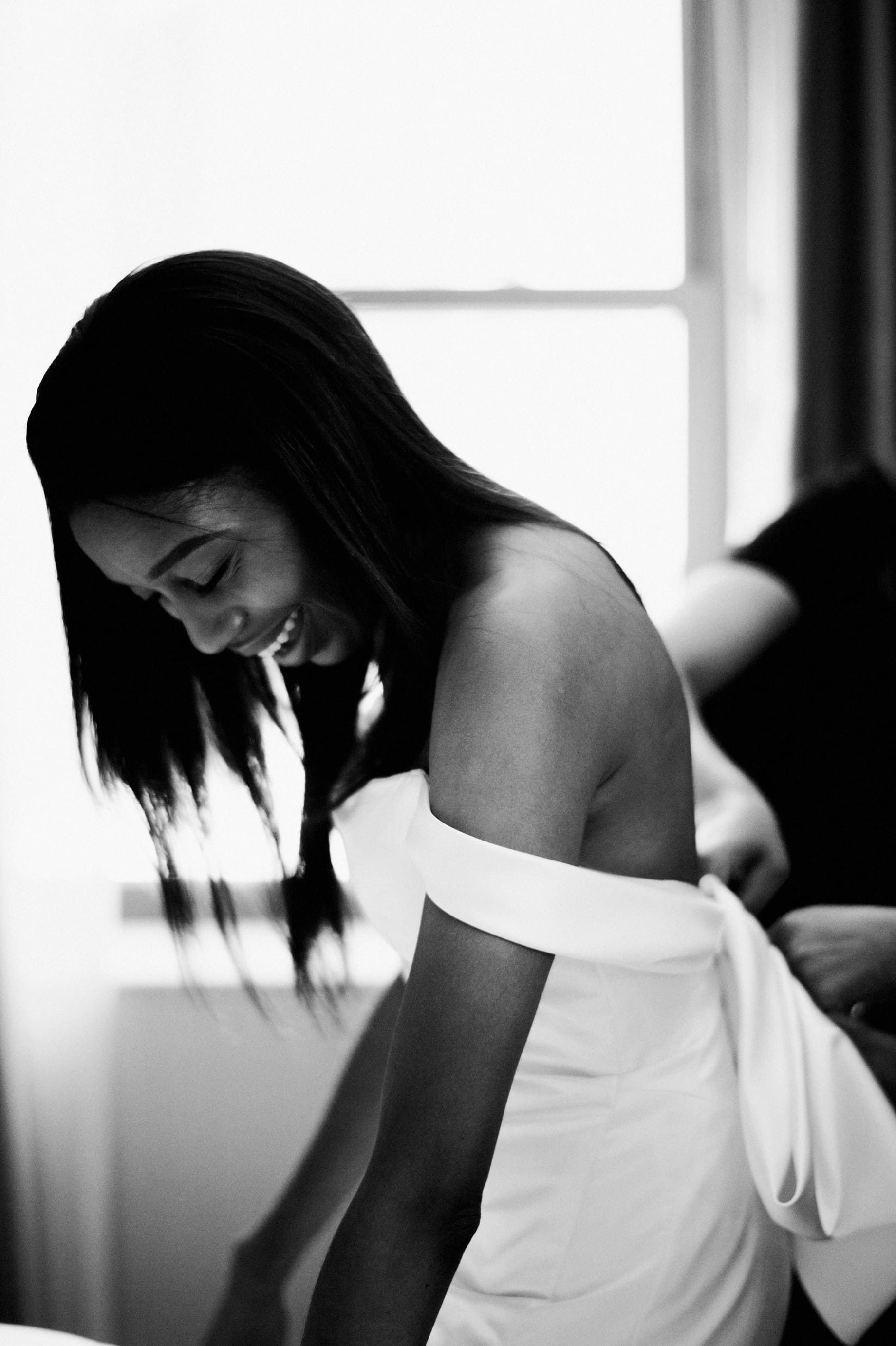 black and white photo of bride getting dress by Detroit wedding photographer Heather Jowett