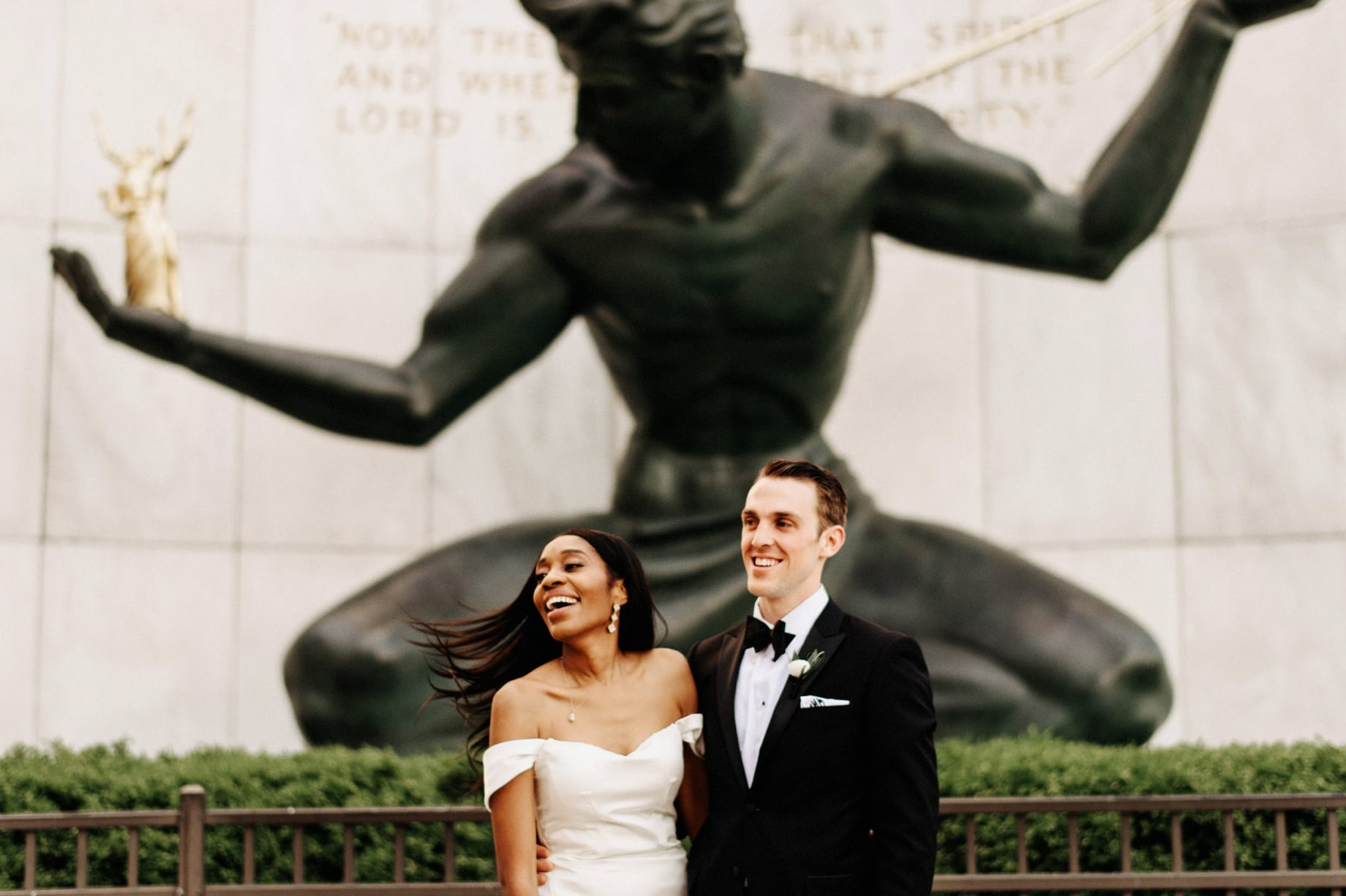 bride and groom laughing in front of spirit of detroit