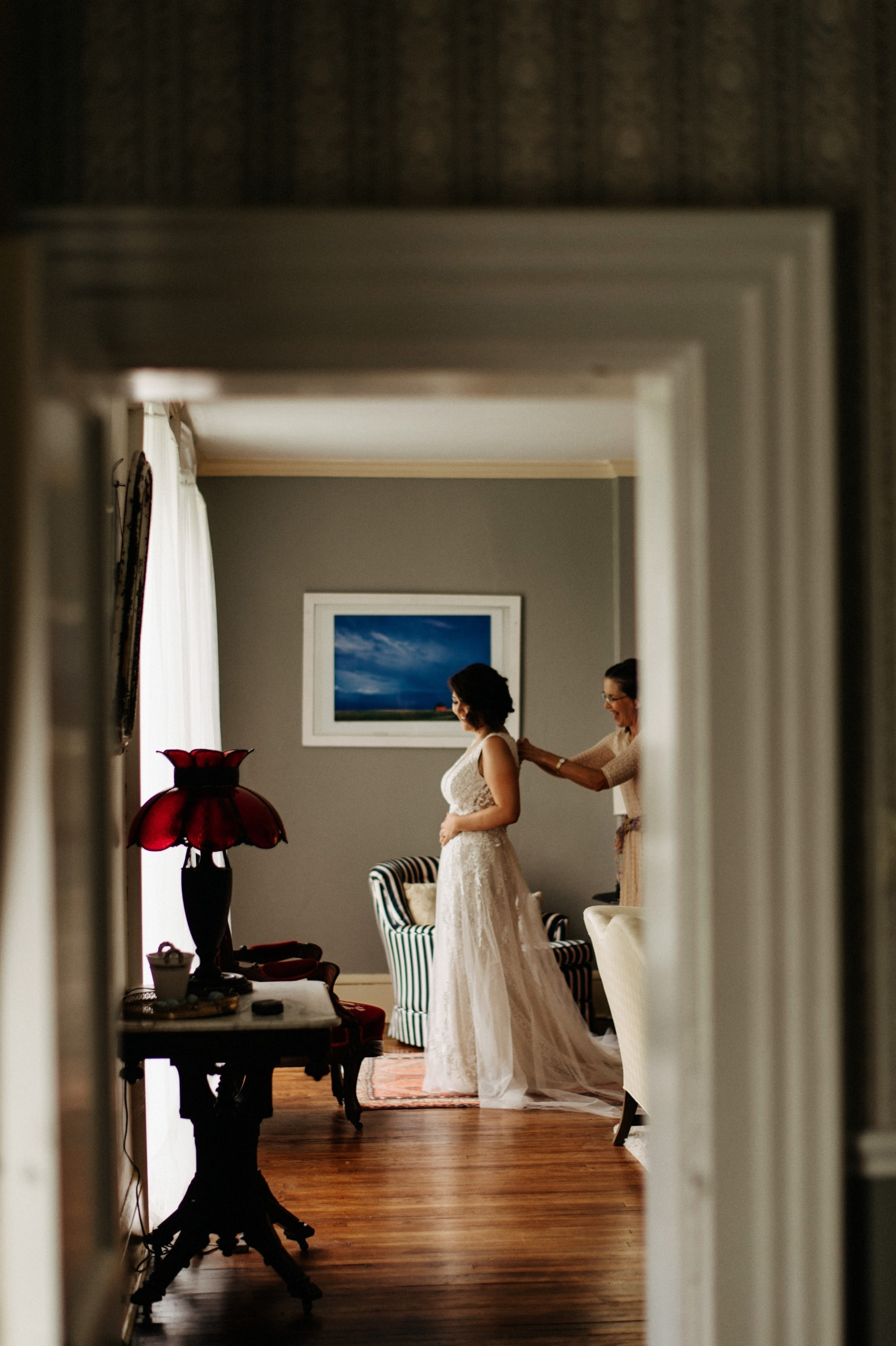 bride being helped into dress at front room of orchard house bed and breakfast