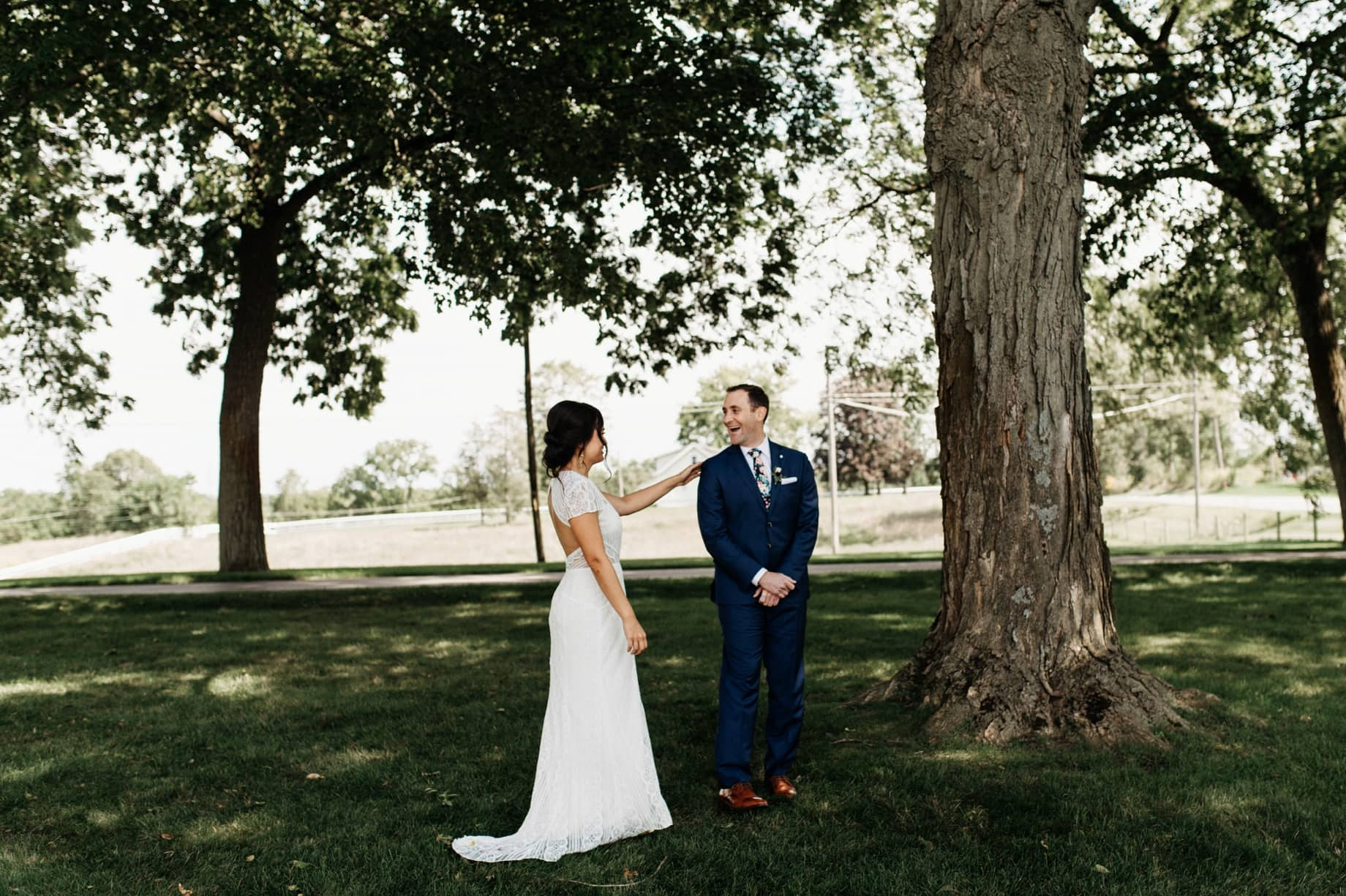 bride and groom sharing first look on the front lawn of zingermans cornman farms