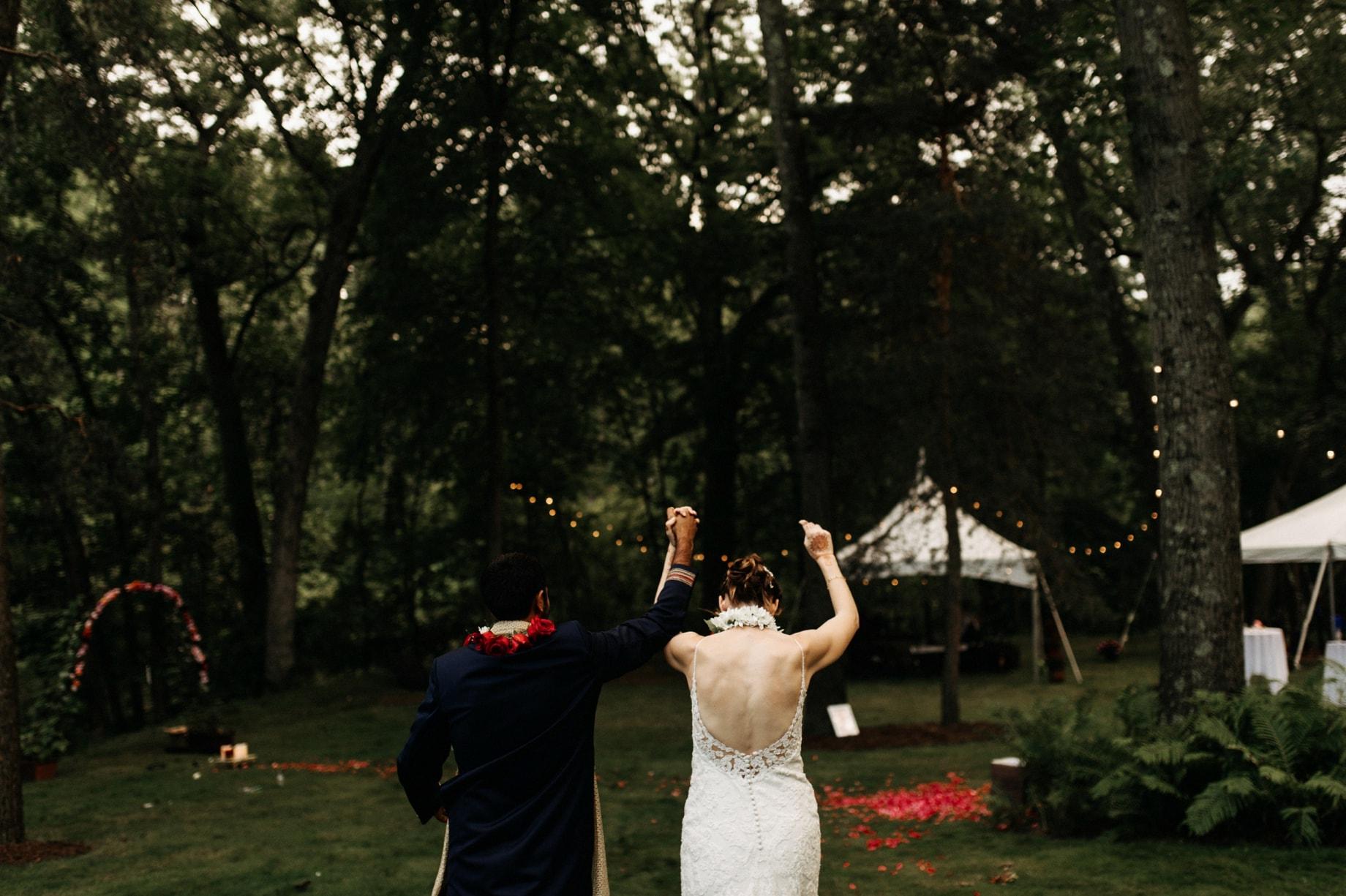 bride and groom entering their backyard wedding reception