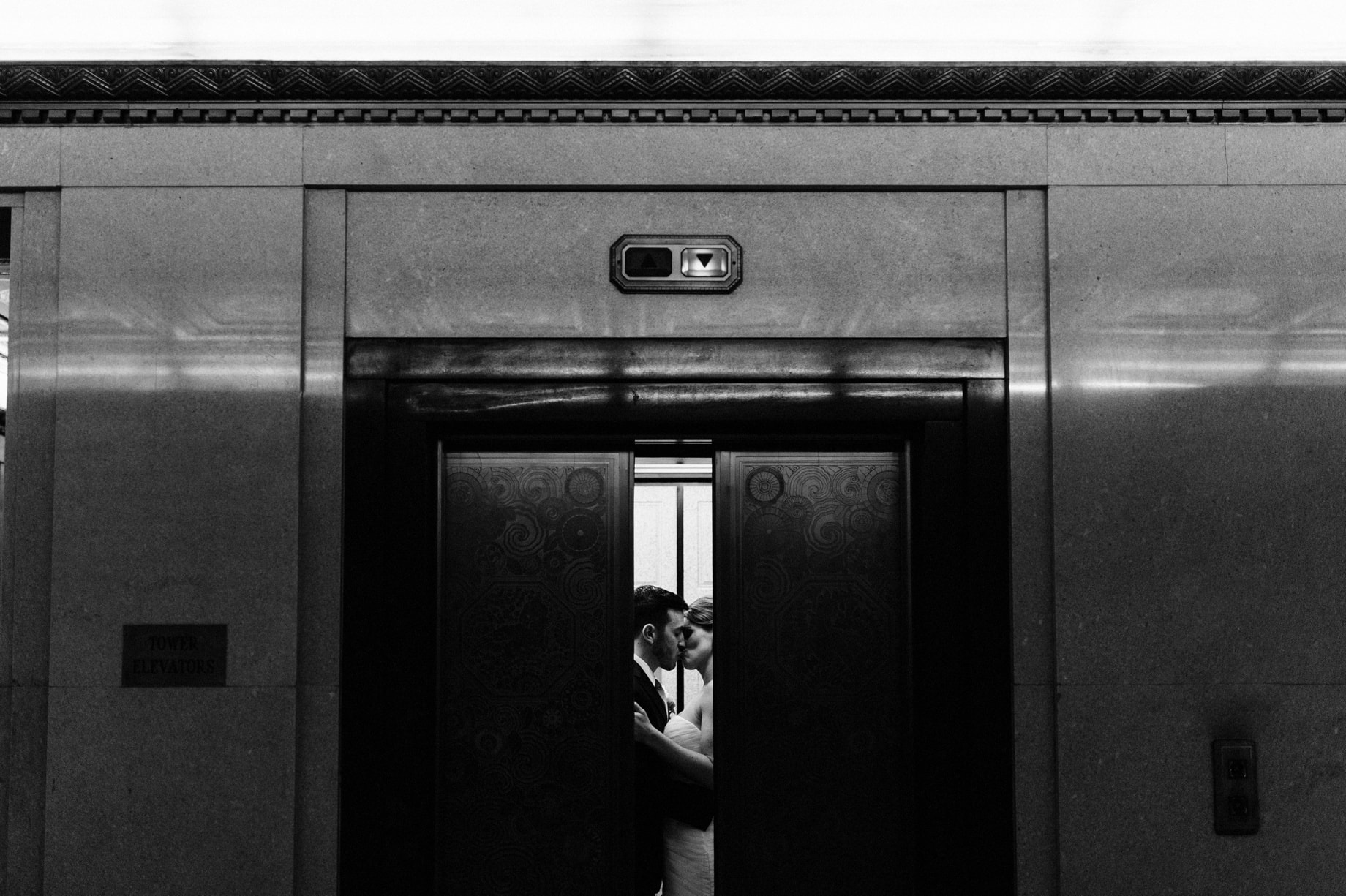 bride and groom in an elevatior at the fisher building in detroit