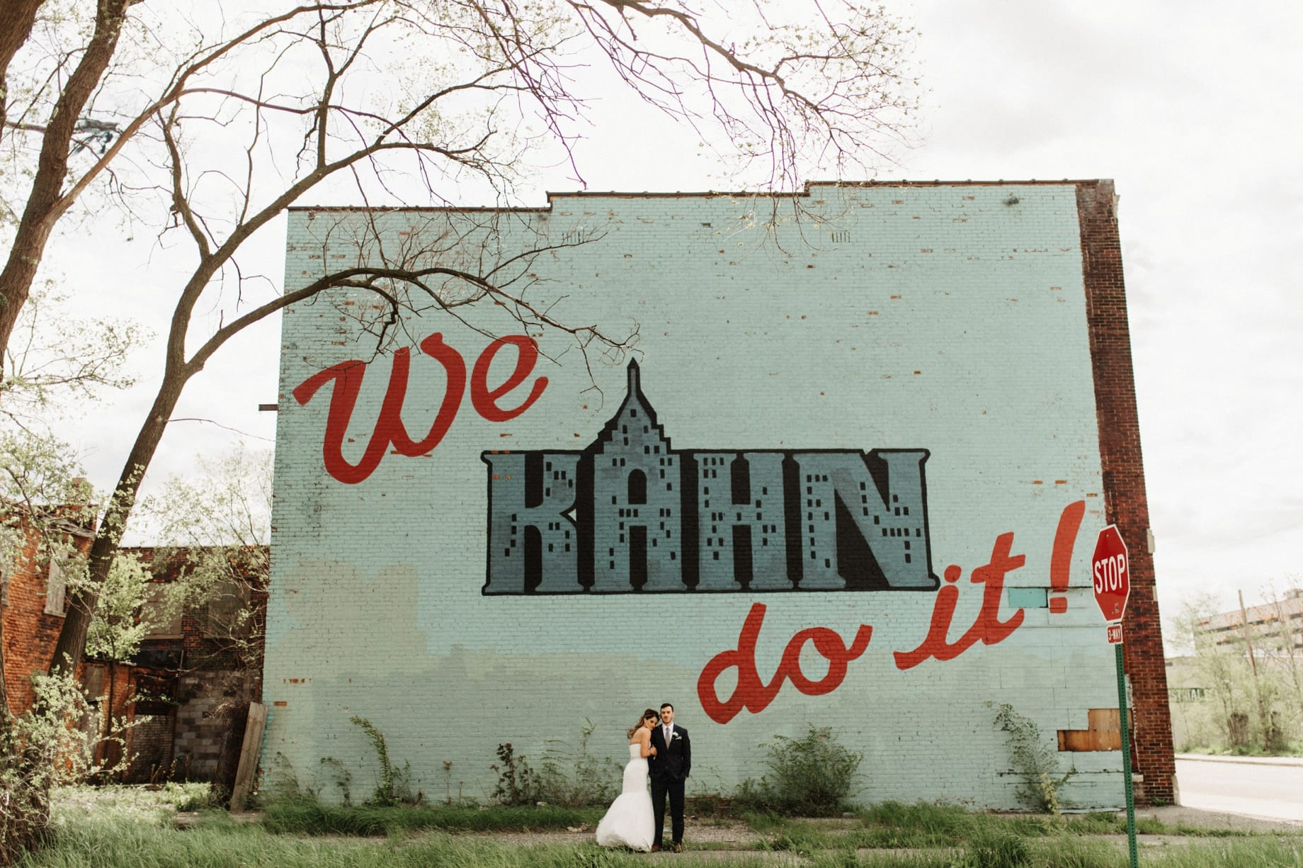 bride and groom pose in front of a detroit mural by wedding photographer heather jowett