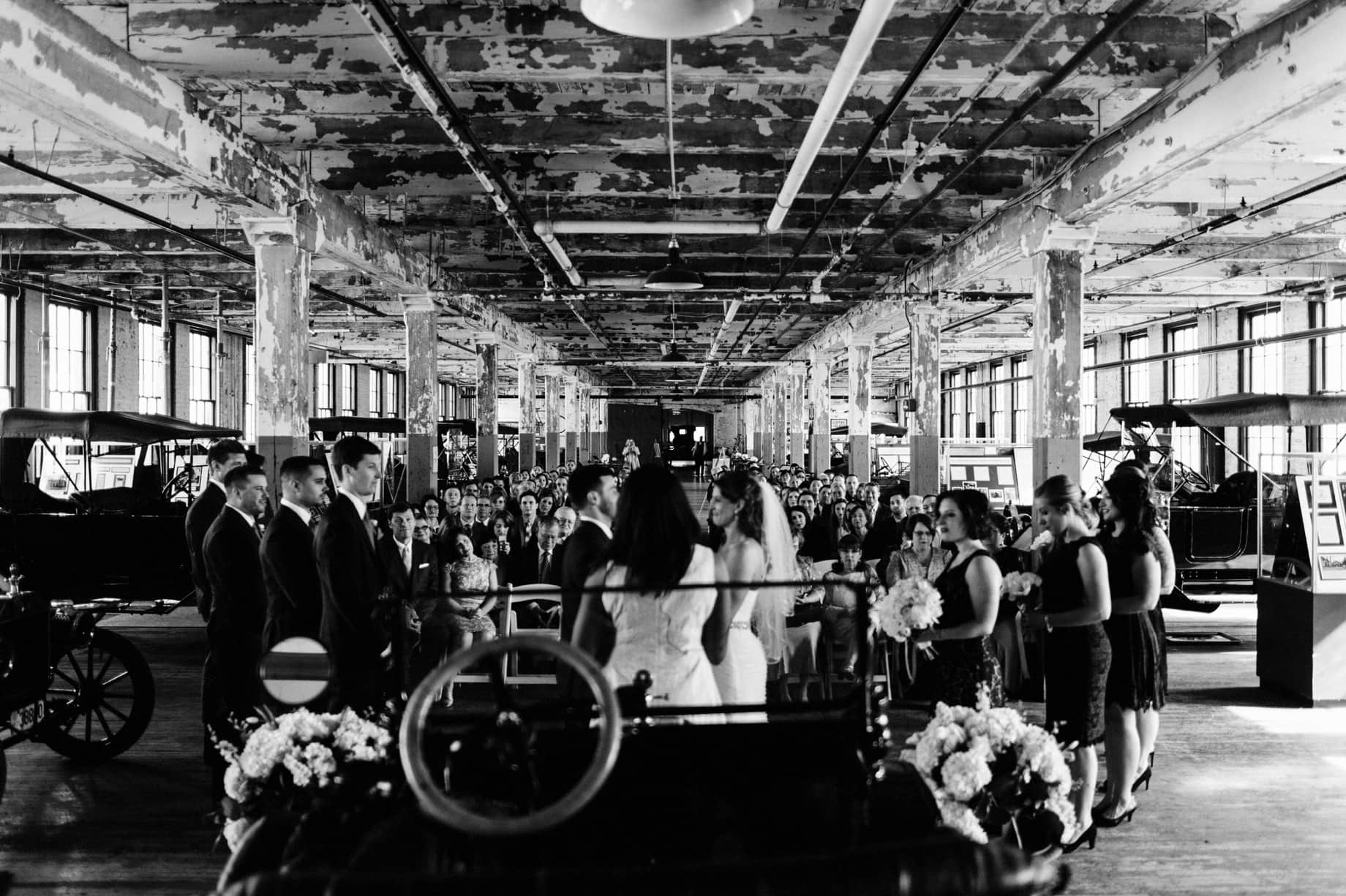 family and friends look on as bride and groom are married at the ford piquette plant in detroit michigan by wedding photographer heather jowett