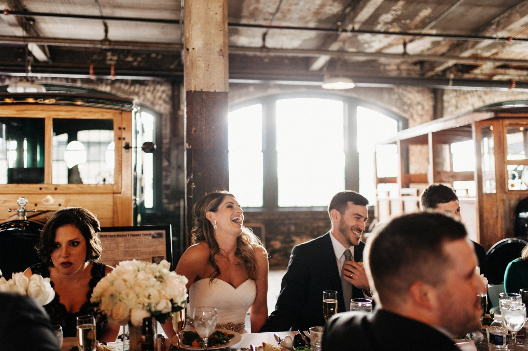 bride and groom laughing at toasts by Detroit Wedding photographer Heather Jowett