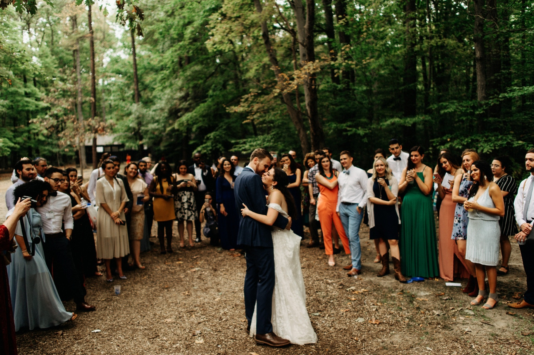 bride and groom surrounded by loved ones during their first dance