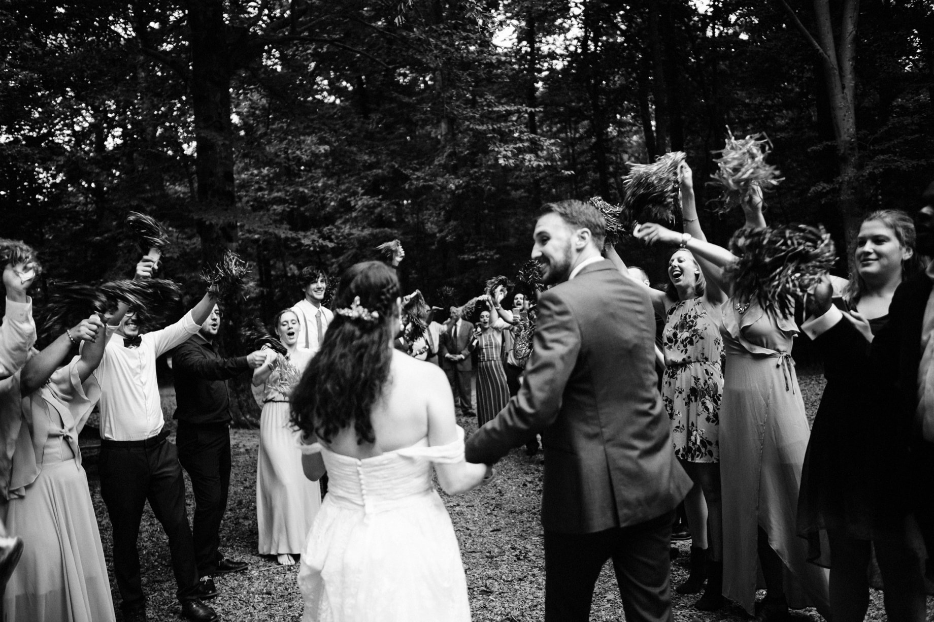 bride and groom exit while guests wave pom poms